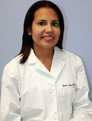 Carla Leon, DDS, dentist at Telegraph Dentists, standing in front of blue wall